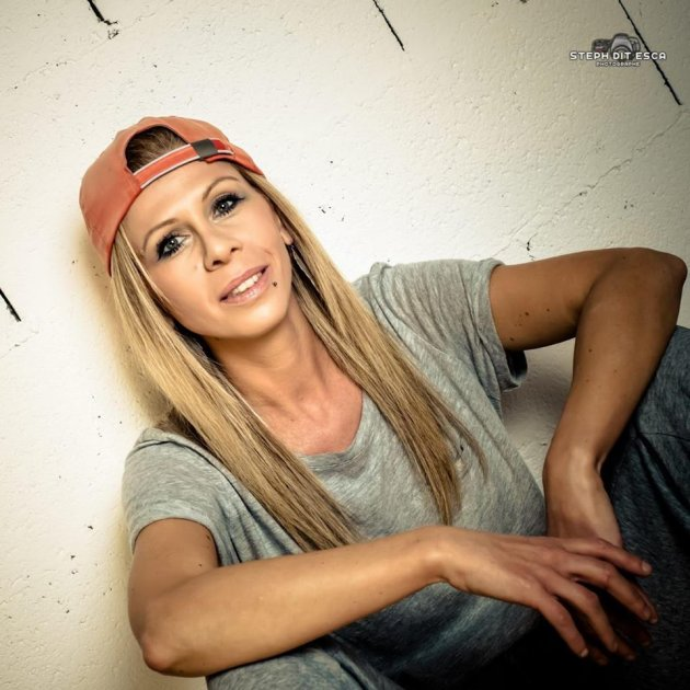 Women with red Cap, blonde Hair, Short grey Shirt sitting in front of a white wall