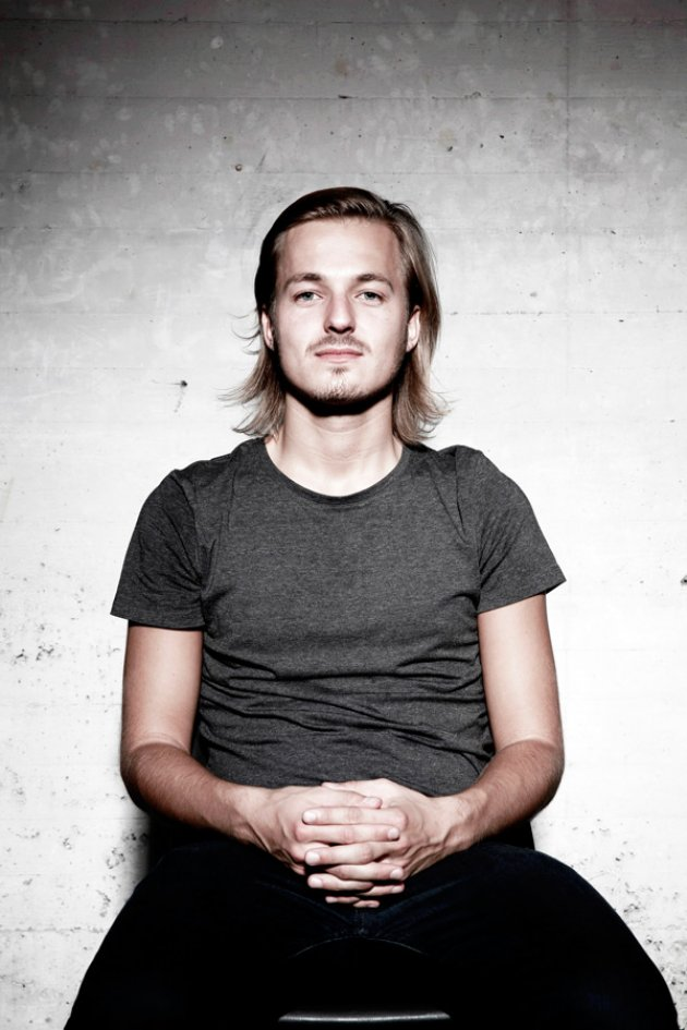 Porträt Bild Konstantin Sibold, graues Shirt, T-Shirt, lange Haare, Blond, Schnäuzer, Adams Apfel